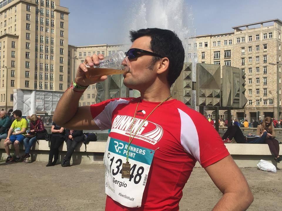 Läufer trinkt Bier im Ziel